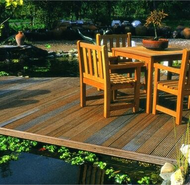picture of wooden garden furniture on hardwood decking, that leads onto a pond.