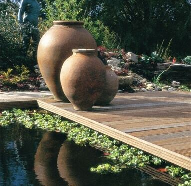3 big heavy pots on the corner of hardwood decking that leads out to a pond.