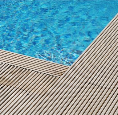 close up of hardwood decking on the corner of a pool.