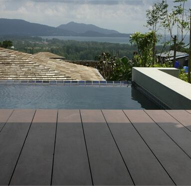 close up view of hardwood decking leading upto a pool that overlooks a beautiful landscape.