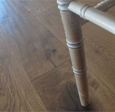 close up of a chair leg sitting on hardwood flooring.