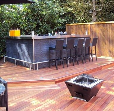 view of hardwood decking with different levels, on the highest level is a bar with a firepit on the lowest level.
