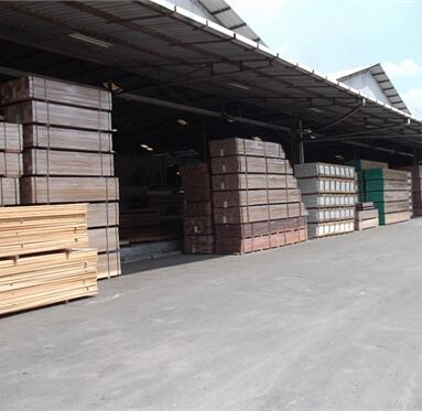 hardwood and softwood stacked up under a canopy outside of a warehouse.