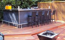 outside bar with chairs on decking board supplied by Direct Timber.