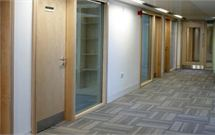 Photo of a hallway with multiple timber doors showing the timber products of James Latham